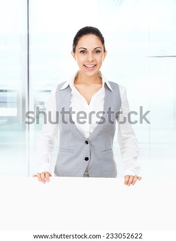 businesswoman holding a blank white card board, signboard, showing an empty bill board, young business woman happy smile in modern office - stock photo