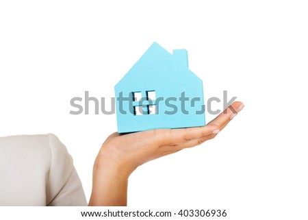 Businesswoman holding a blue paper house - stock photo