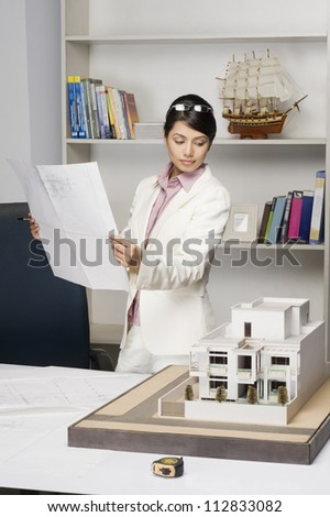 Businesswoman holding a blueprint and looking at a model home in an office - stock photo