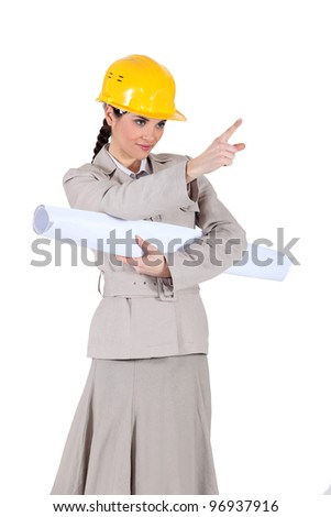 businesswoman holding a blueprint and pointing at something