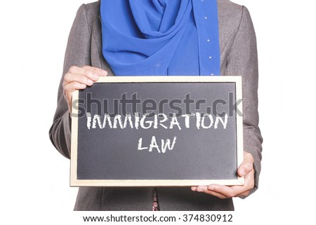 Businesswoman holding a chalk board written Immigration Law - stock photo