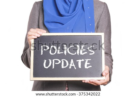 Businesswoman holding a chalk board written Policies Update - stock photo