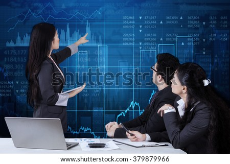 Businesswoman holding a digital tablet while delivering a presentation to her colleagues during a meeting and explaining financial graph - stock photo