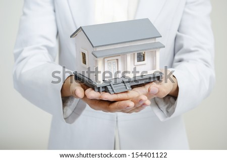 Businesswoman holding a house in hands