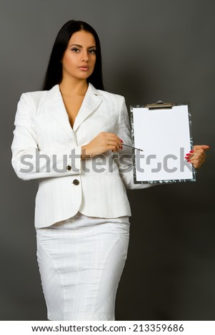businesswoman holding a pen requesting a signature on a document Isolated on gray background - stock photo