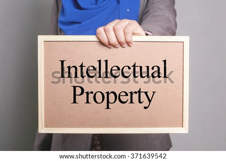 Businesswoman holding a soft board written Intellectual Property - stock photo