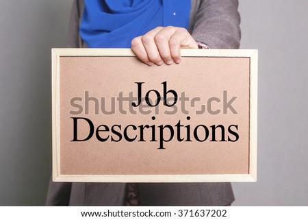 Businesswoman holding a softboard written Job Descriptions - stock photo