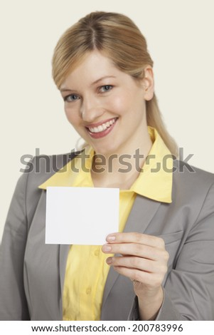 Businesswoman holding blank note, smiling.