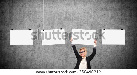 Businesswoman holding blank poster over head. Three blank poster hanging on a rope - stock photo