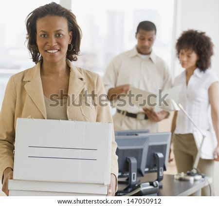 Businesswoman holding box in office