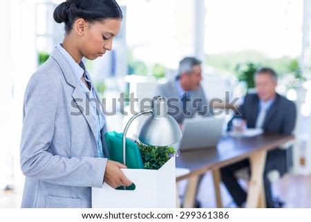 Businesswoman holding box with her colleagues behind her in office - stock photo