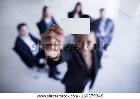 Businesswoman holding business card up to camera - stock photo