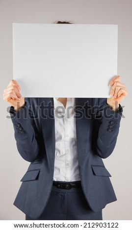 Businesswoman holding card over face on grey background