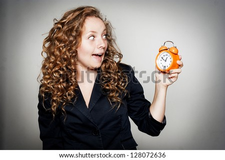Businesswoman holding clock - stock photo