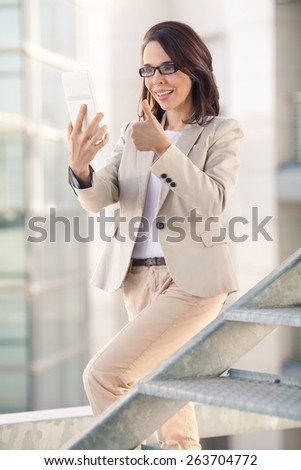 Businesswoman holding digital tablet with her thumb up - stock photo