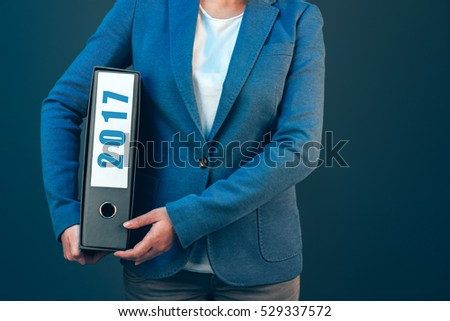 Businesswoman holding 2017 document binder with archived files for the past business year