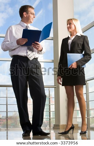 Businesswoman holding document case looking to his colleague in the building with glassy walls