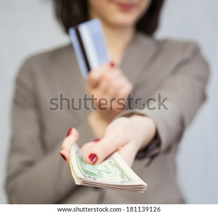 Businesswoman holding dollars and credit card, grey background - stock photo