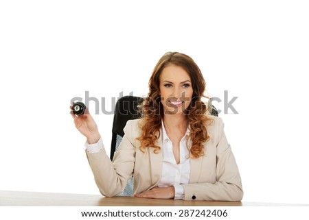 Businesswoman holding eight billiard ball by a desk. - stock photo
