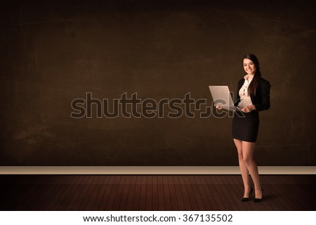 Businesswoman holding high tech laptop on brown background with copyspace - stock photo