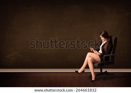 Businesswoman holding high tech tablet on brown background with copyspace