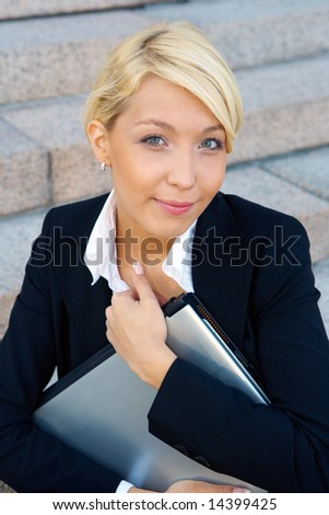 Businesswoman holding laptop computer, looking at camera - stock photo