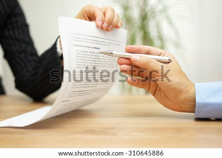 businesswoman holding legal document and  wants an explanation about article in contract - stock photo
