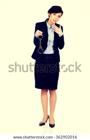 Businesswoman holding metal handcuffs. - stock photo