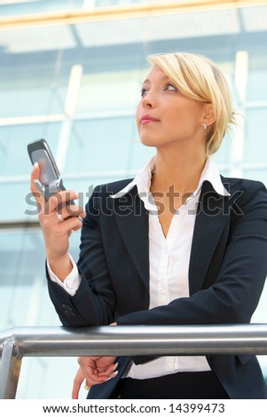 Businesswoman holding mobile phone, looking up - stock photo