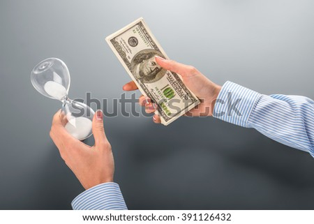 Businesswoman holding money and hourglass. Female holds cash and hourglass. Value what you have. Take one or loose both.