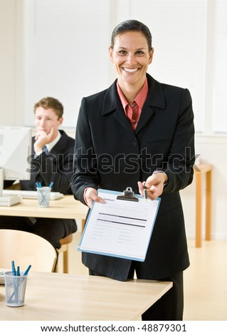 Businesswoman holding out clipboard and pen - stock photo