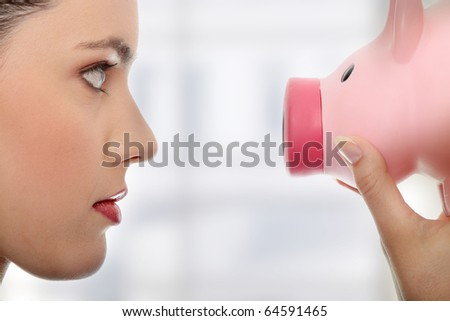 Businesswoman holding piggy bank.
