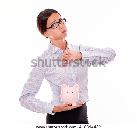 Businesswoman holding pink porcelain piggy bank with disapproval and a thumb down gesture wearing her hair back and a button down shirt while looking at camera on a white background - stock photo