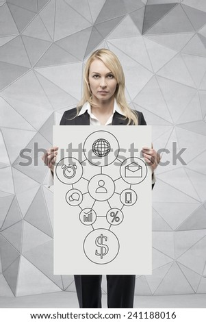 businesswoman holding poster with drawing business map on wall - stock photo