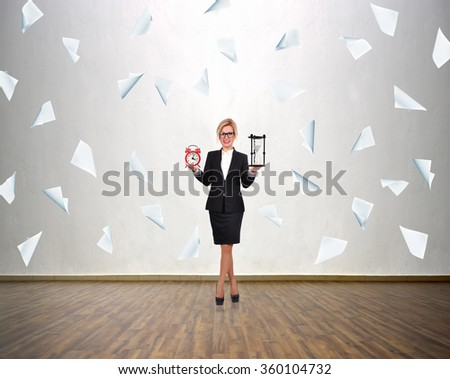 Businesswoman holding sandglass and alarm clock in hand. Falling many blank paper. - stock photo
