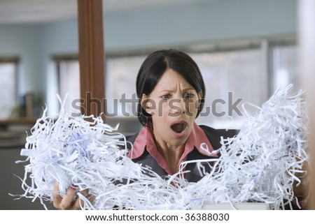 Businesswoman holding shredded papers