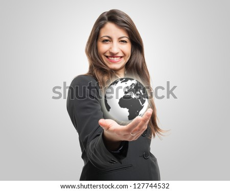 Businesswoman holding the world in her hand - stock photo
