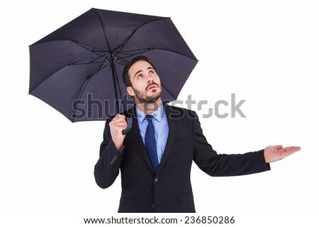 Businesswoman holding umbrella while testing if it rains on white background - stock photo