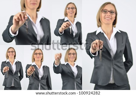 businesswoman holding up a pair of keys - stock photo
