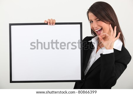 Businesswoman holding white board - stock photo