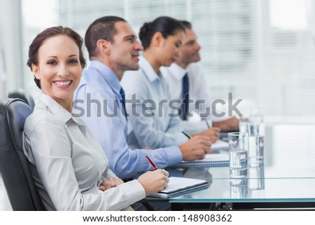 Businesswoman  in bright office smiling at camera while her colleagues listening to presentation