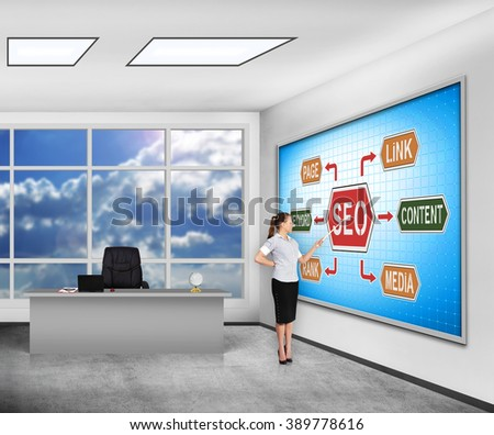businesswoman in classroom pointing on  plasma panel with seo concept - stock photo