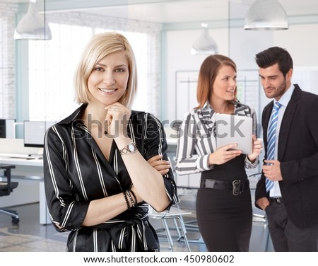 Businesswoman in front at office with working colleagues in background.