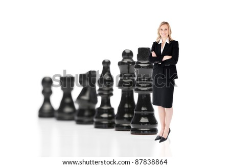 Businesswoman in front of black chess pieces on white background - stock photo