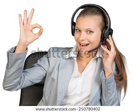 Businesswoman in headset making okay gesture, her other hand on headset speaker, looking at camera, her mouth open. Isolated over white background - stock photo
