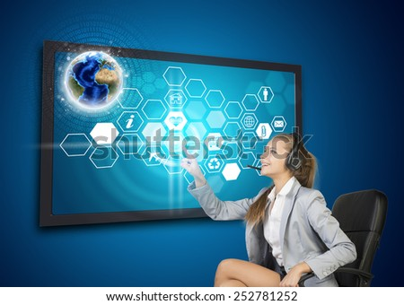 Businesswoman in headset pressing touch screen button on virtual interface with Globe and honeycomb shaped icons, on blue background. Element of this image furnished by NASA - stock photo