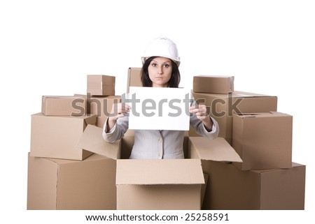 businesswoman in helmet with blank card standing in carton box - stock photo