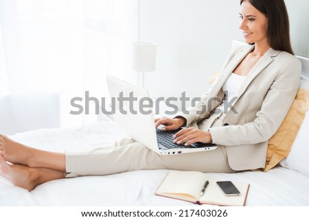 Businesswoman in hotel room. Beautiful young businesswoman in suit working on laptop and smiling while sitting in bed at the hotel room - stock photo