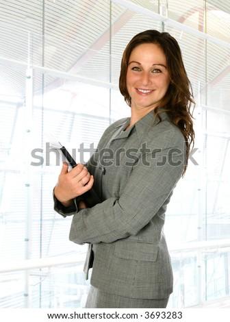 Businesswoman in modern corporate interior, file in hand. - stock photo