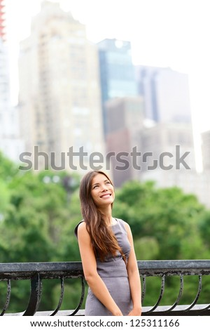 Businesswoman in New York City Central Park standing looking up at copy space with skyscraper buildings from Manhattan skyline in background. Young female professional. Mixed Asian / Caucasian race. - stock photo
